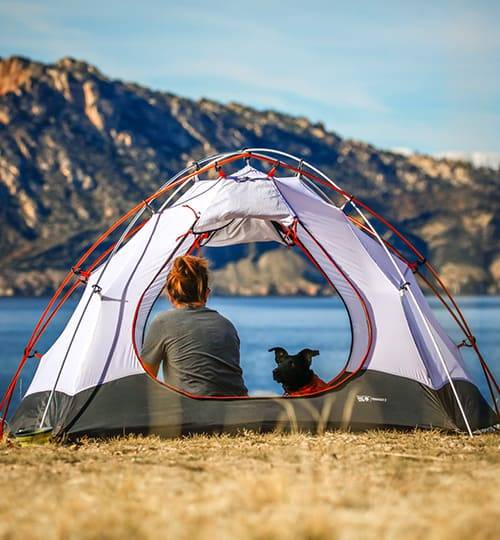 woman and dog in a tent looking at a lake and a mountain