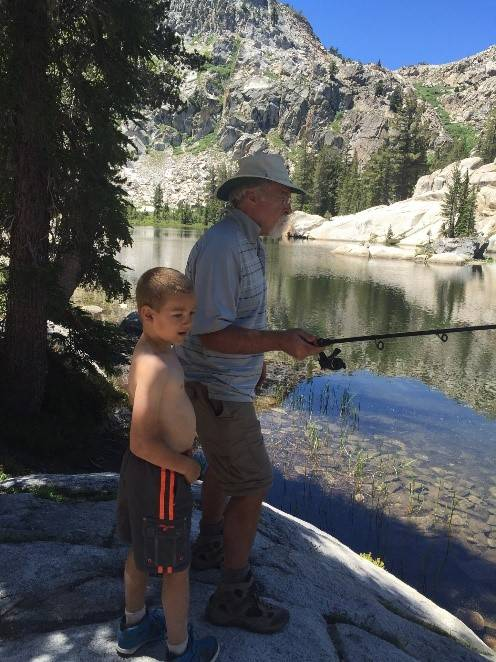young boy fishing with is grandfather in the mountains.