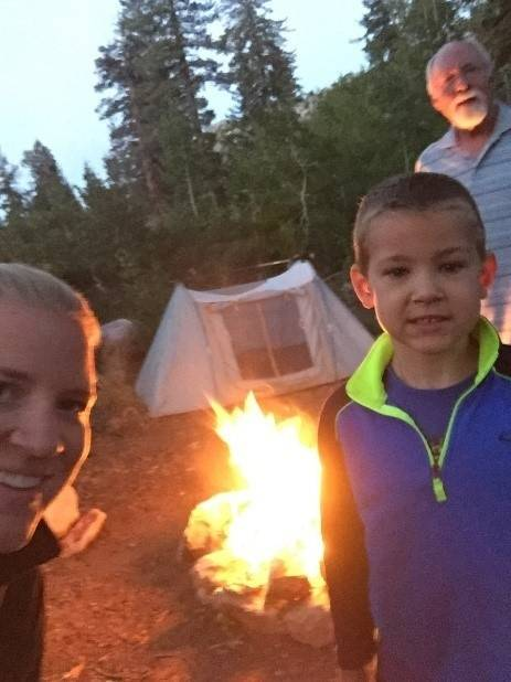 campfire with man, woman and boy. Tentin the background.