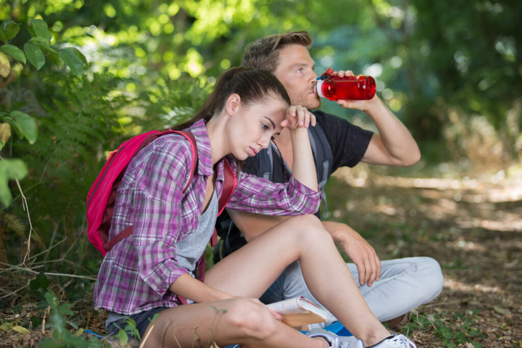 young couple resting on a hike. man is drinking from a water bottle.
