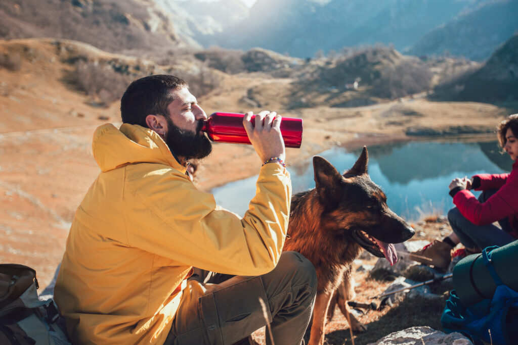 people taking a break on a hiking trail with their dog. Man drinking water.