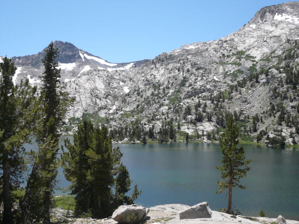 Rae Lake California steep mountain with a tree, lake, and rocks.