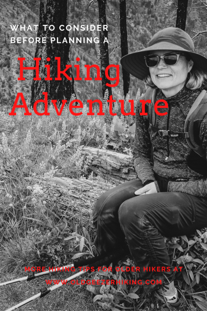 woman sitting on a log in hiking clothes getting ready to go on a hiking adventure.