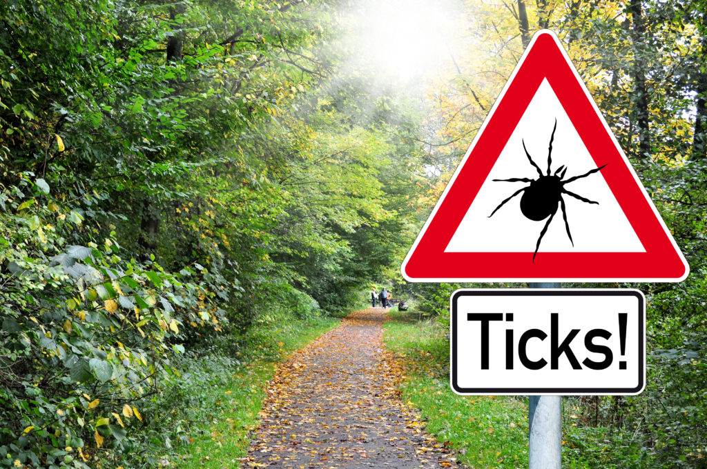 beware of ticks on a sign in the forest.