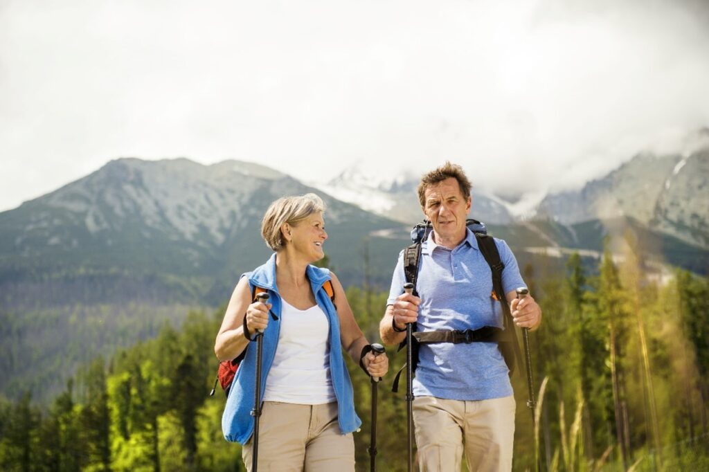 man and woman hikers over 50 hiking with hiking poles.