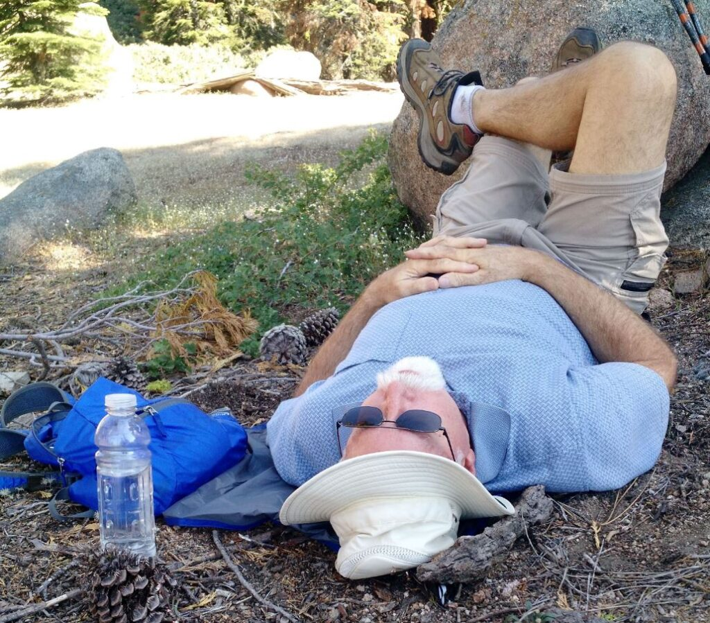 man laying down on a personal sized backpacking tarp while hiking.