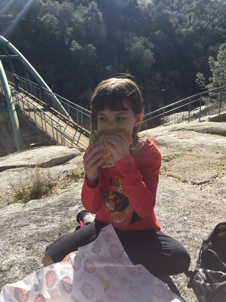 girl eating on a rock by a bridge while hiking.