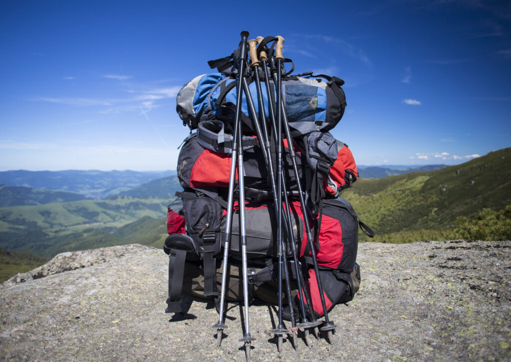 several trekking poles leaning against backpacks