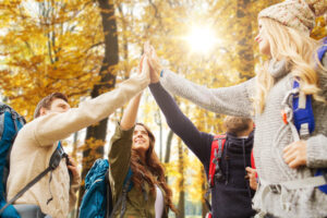 friends making high five on a hike in autumn.