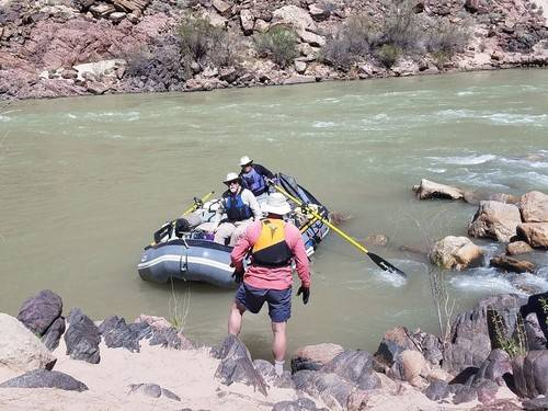 Older hiker in a resuce boat on the Colorado River in the Gran Canyon.