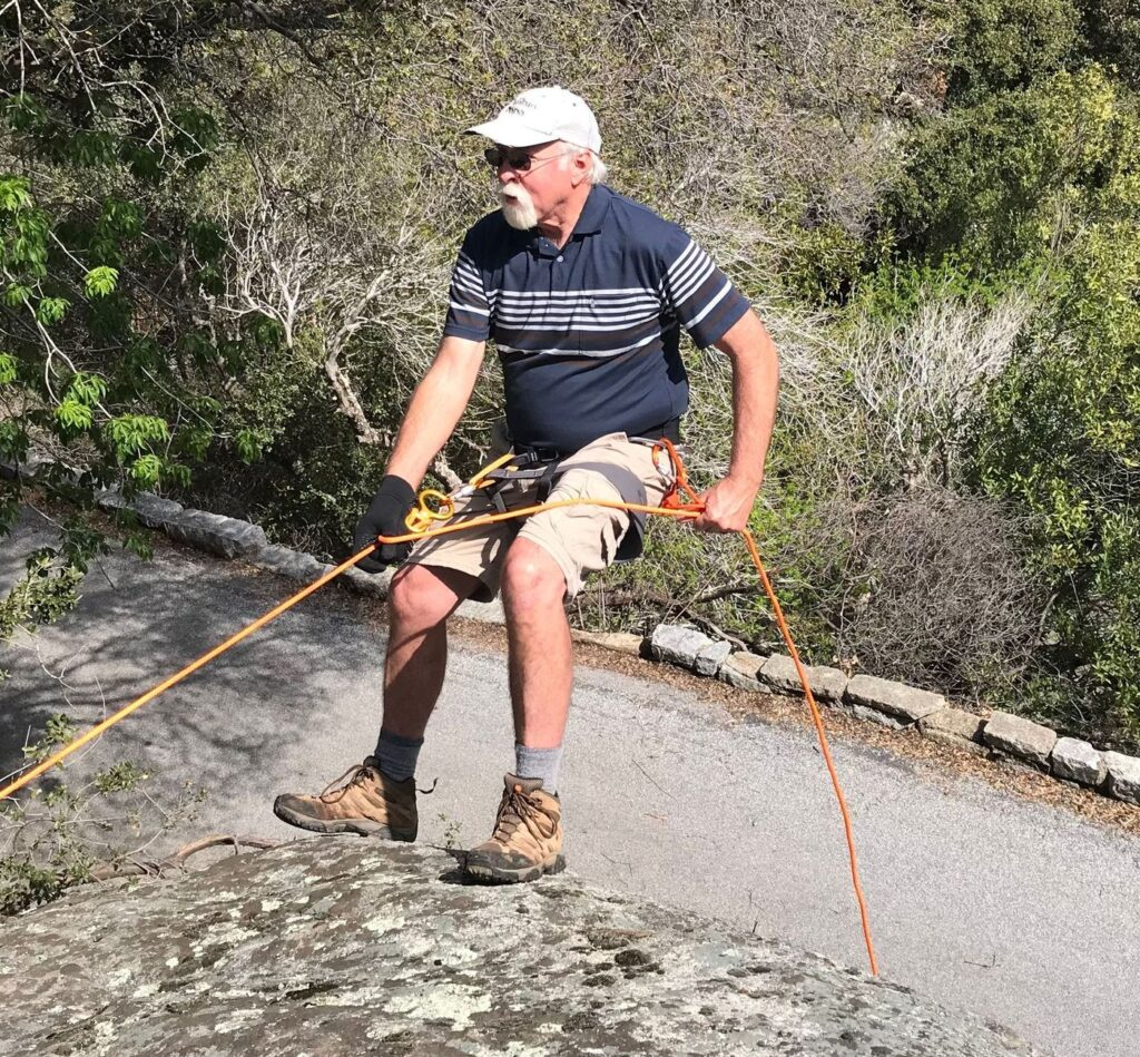 mature hiker rappelling down the side of a rock.