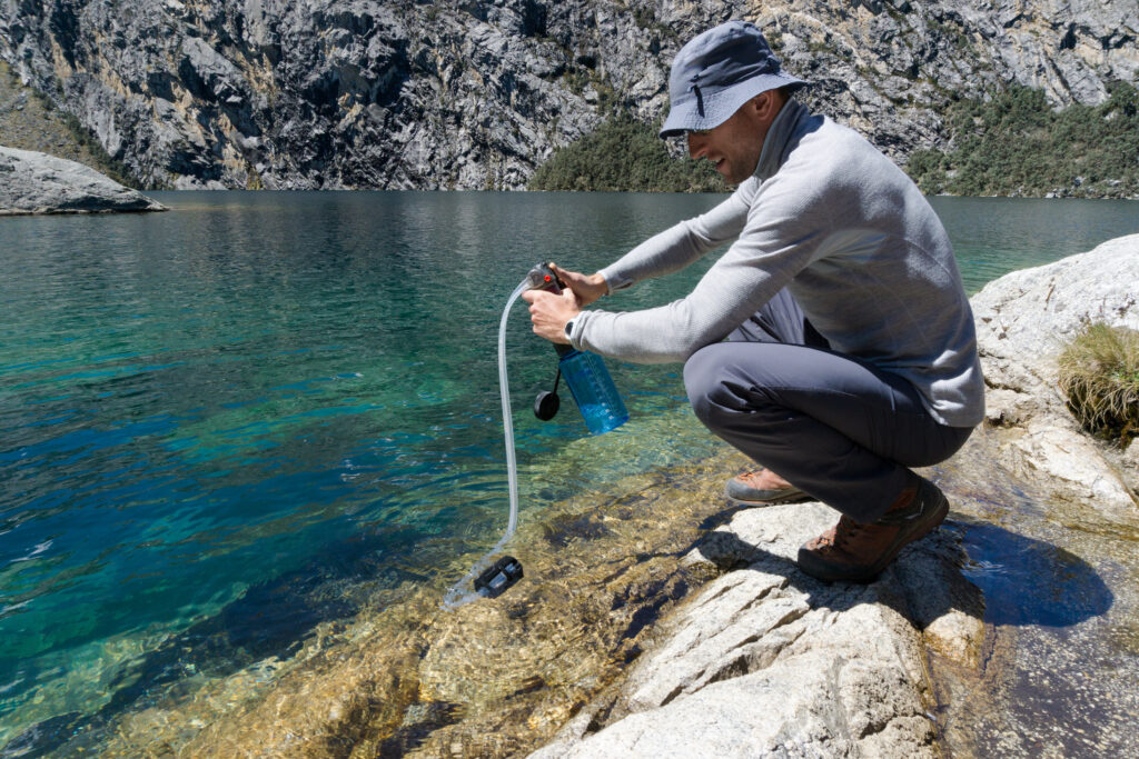 man showing how to purify water at a lake in the mountains