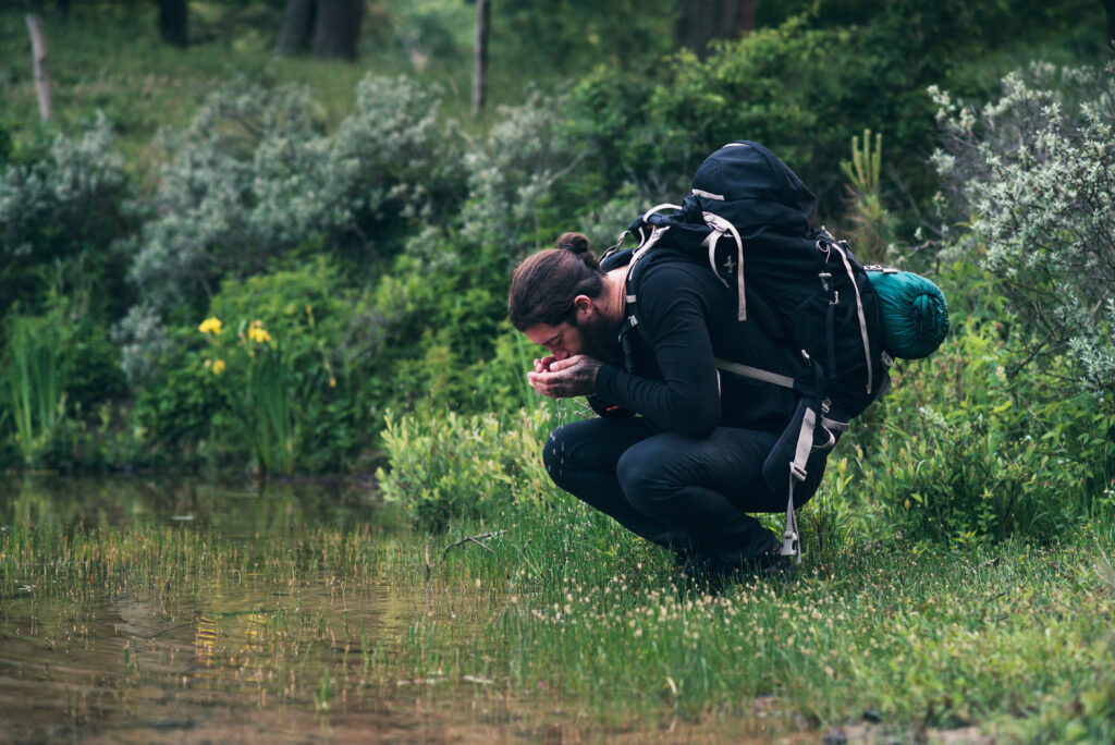 man with backpack drinking water from a mountain lake.