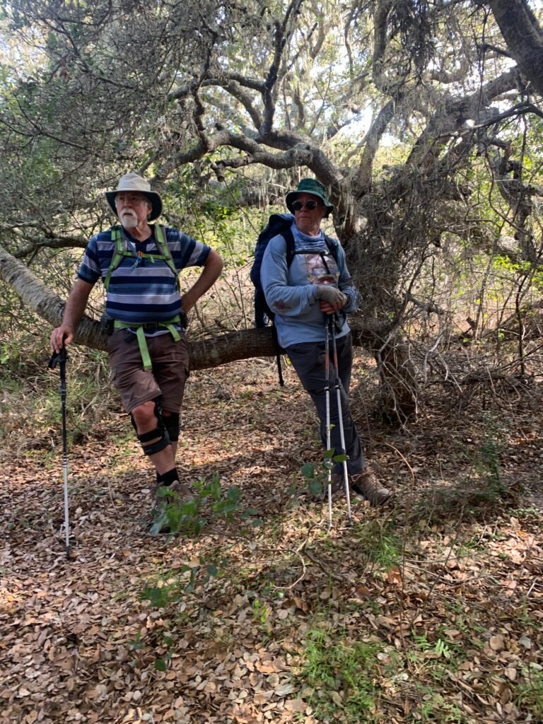 Mature Hikers taking a break leaning against a tree