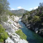 San Joaquin River Gorge in Fresno County California with stream, trees, rocks, and mountains.