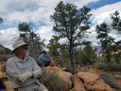 older hikers sitting on a rock