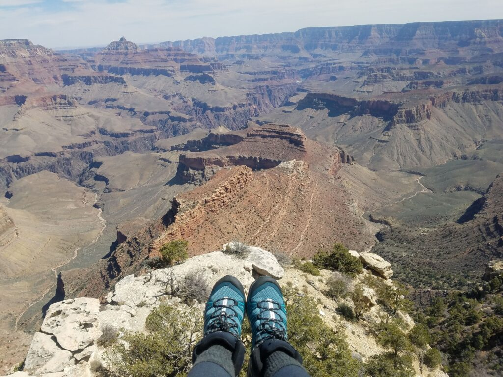 woman's feet on a rock overlooking the grand canyon