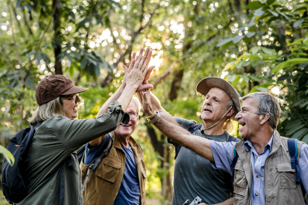 group of older hikers giving high fives