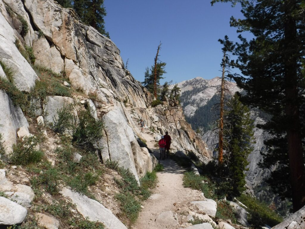 hiking trail with a cliff on one side and mountains on the other side.