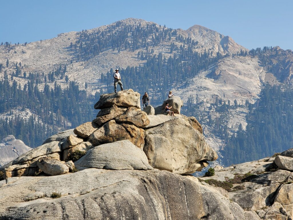 hikers on top of watch tower rock in Sequoia National Park.