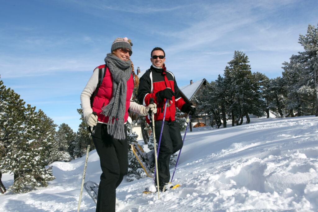 couple staying warm walking in snowshoes.